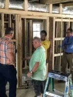 Four people talking in a house under construction