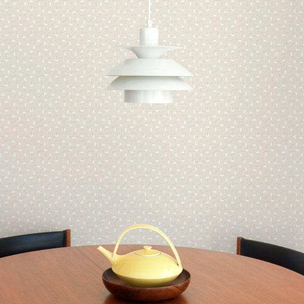 Papel pintado Primitive Micro en fondo beige diseñado por Jaime Hayon para England&Co colocado en la pared del comedor