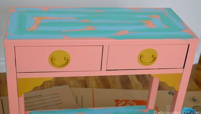 painting blue paint onto a pink console table