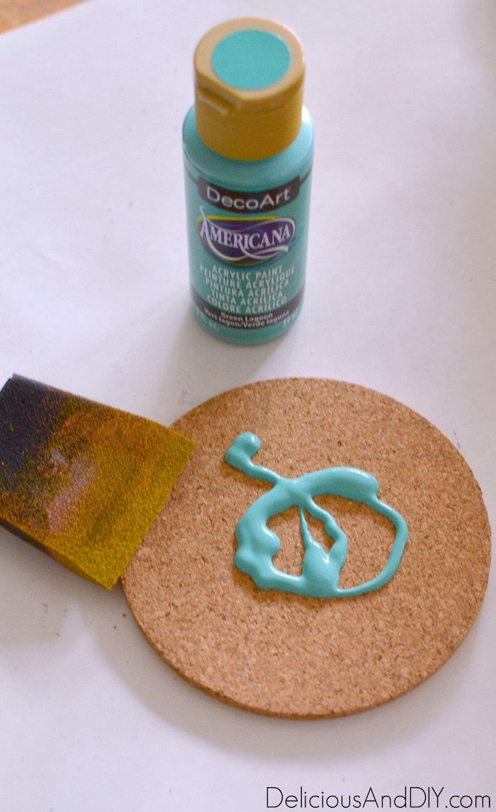 cork coaster being painted in a teal color