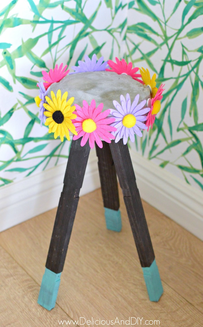 A colorful felt flower concrete plant stand with half turquoise dipped in paint wooden legs