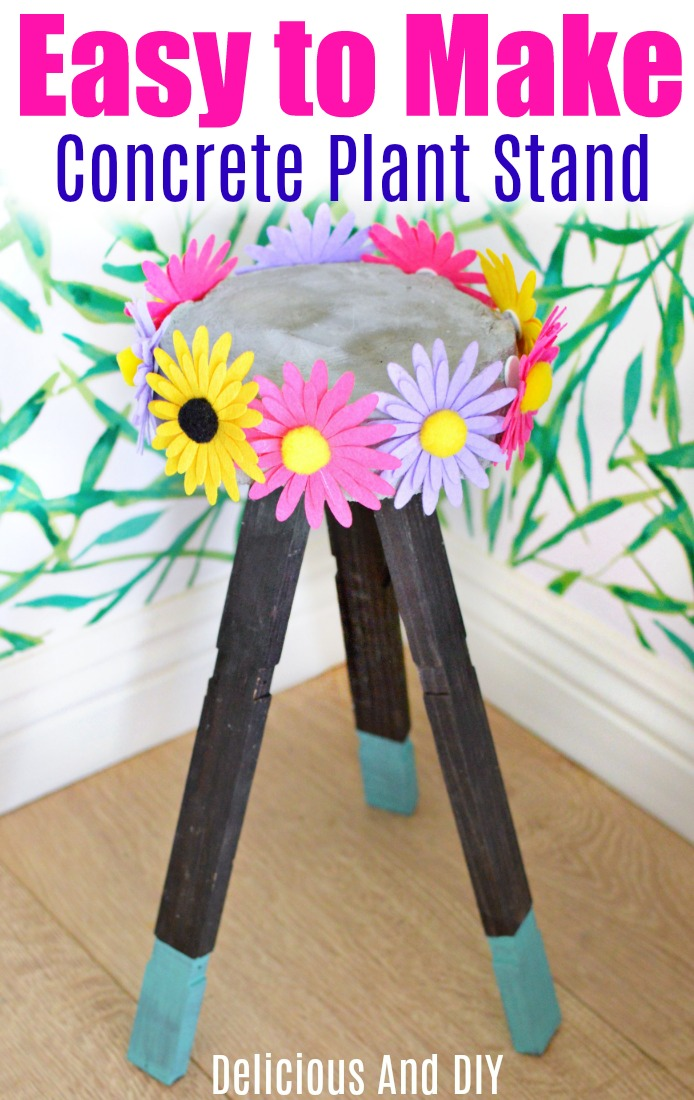 Concrete Plant Stand made with Wooden Legs. The Concrete top has colorful flowers attached all around the sides of it.