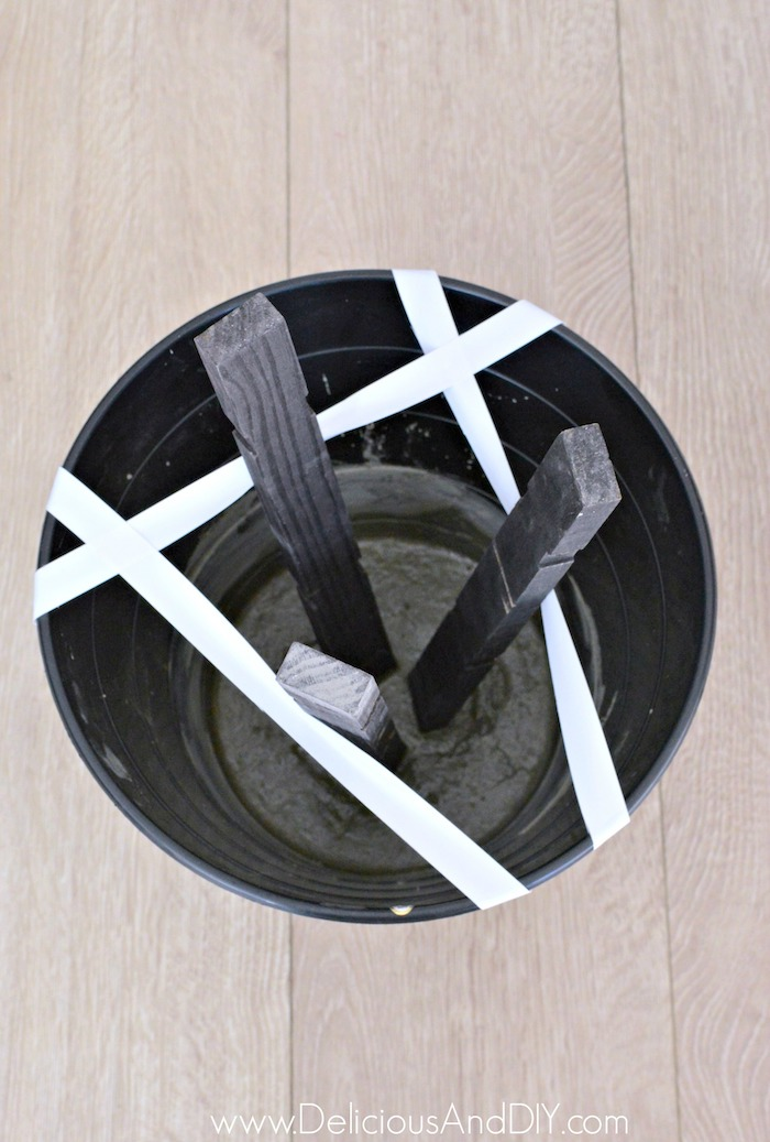 Concrete mixed in a round plastic pin with Wooden Legs inserted into it which is balanced in place by using Tape.