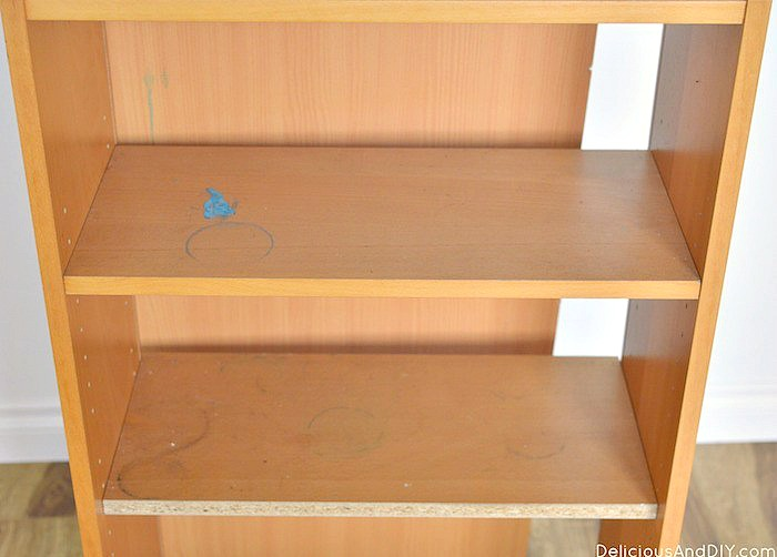 A close up picture of a wooden bookshelf shelves with stains and scratches