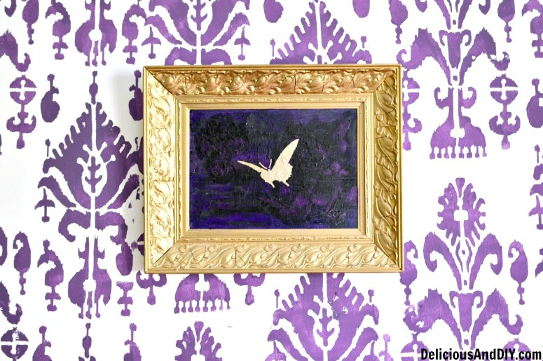 An upcycled thrift store Wall Art with a purple background and a golden butterfly stenciled on top of it.
