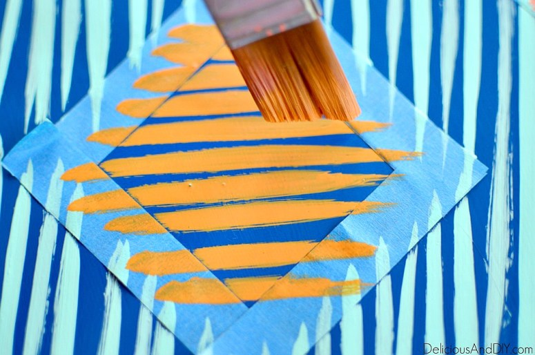 painting orange brushstrokes onto the bar stool