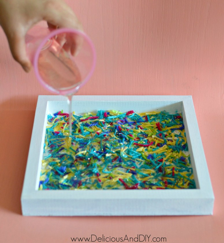 pour the epoxy resin onto the wooden tray and completely cover the yarn with resin
