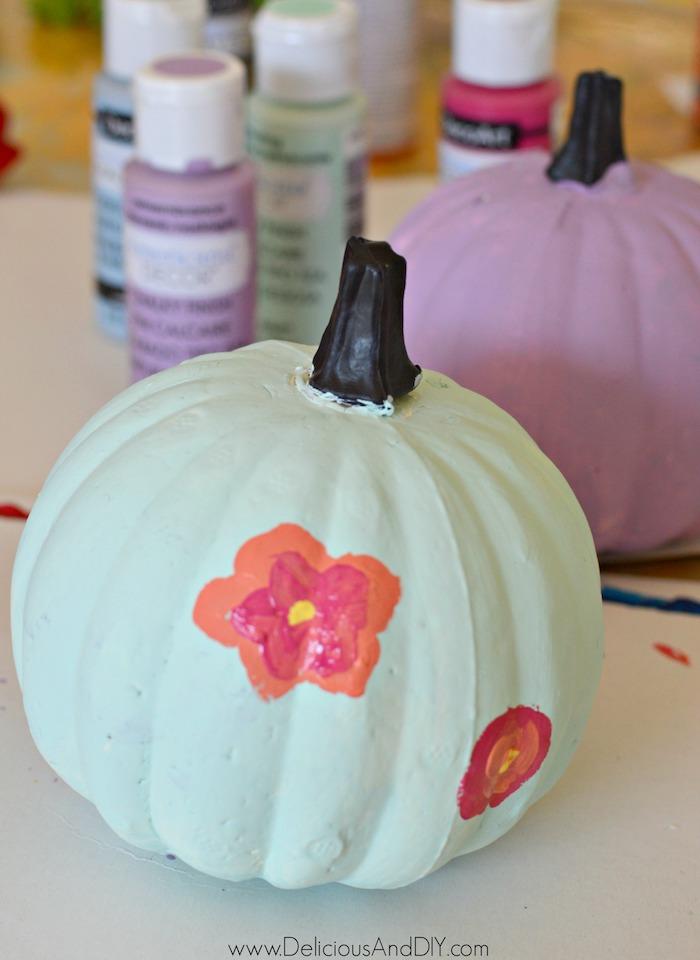 painting flowers onto pumpkins