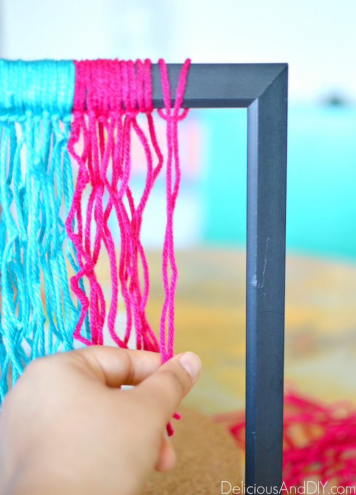 pulling the yarn around the frame tightly to keep it in place