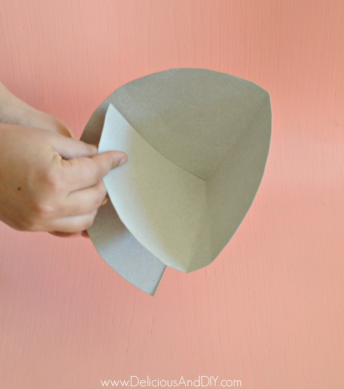 holding paper to make it into a paper cone