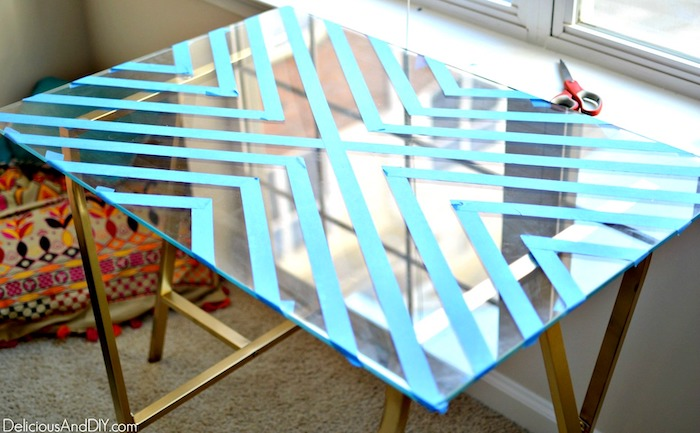 glass table top with masking tape in a triangle pattern