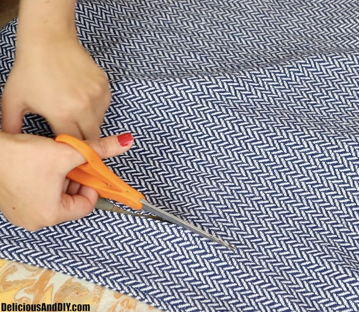 cutting throw blanket with scissors to make covers