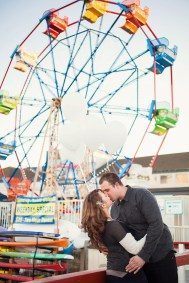 engaged couple with balloons in front of the ferris wheel