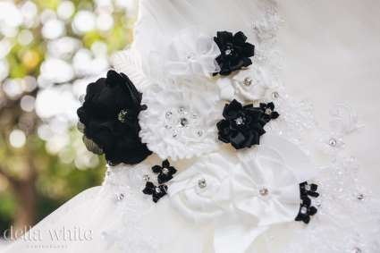 detail of black and white flowers on wedding dress
