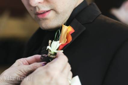 grooms orange calla lily boutonniere getting pinned