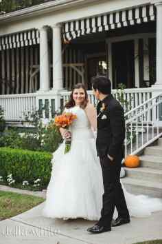 bride and groom in front of christmas house inn