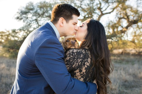 engagement kiss with the couples dog