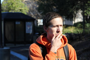 NO BUTTS ALLOWED: Delta student Chris Staggs enjoys a cigarette in the Shima 1 parking lot on Feb. 5. Behind him, the smoking ban sign looms.