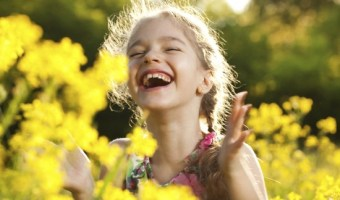 Charming cheerful girl among yellow wildflowers