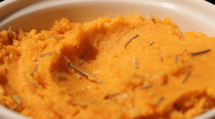 Sweet potatoes are mashed in a bowl with rosemary on top.