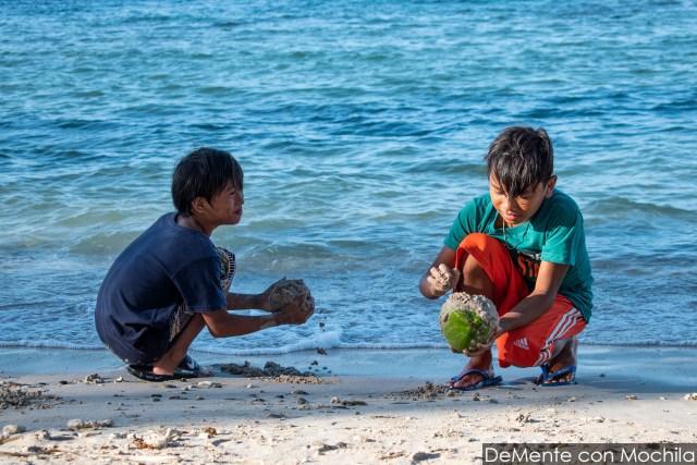 Niño cubriendo un coco con arena.