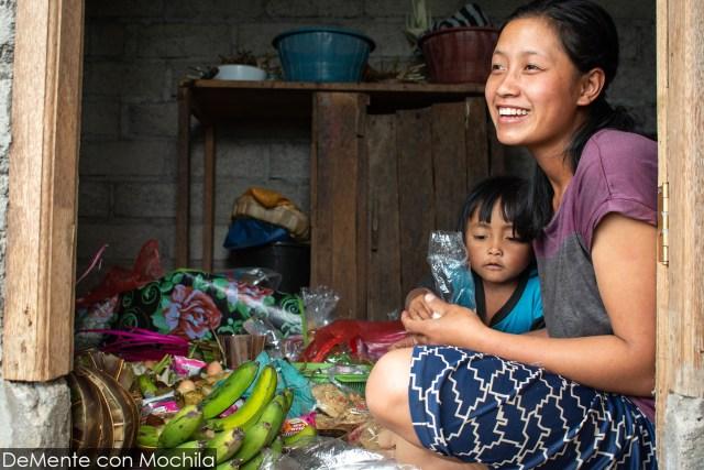 Mujer sentada en el suelo preparando ofrendas.