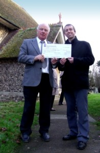 Terry Bishop (right) presenting the cheque to Jim Fletcher, the Rector of All Saints Church
