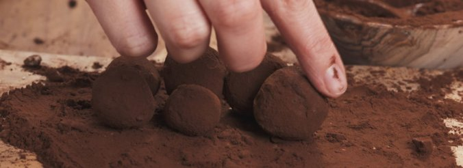 A hand rolls balls of chocolate on top of a chocolate-powder-drenched cutting board.