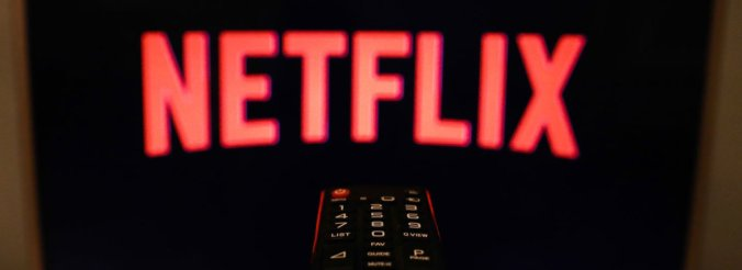 A TV remote control is aimed at a black screen displaying the Netflix logo