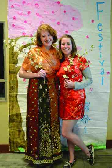Maddy Bellman '18 and a friend pose in front of student artwork while holding cherry blossom flowers.
