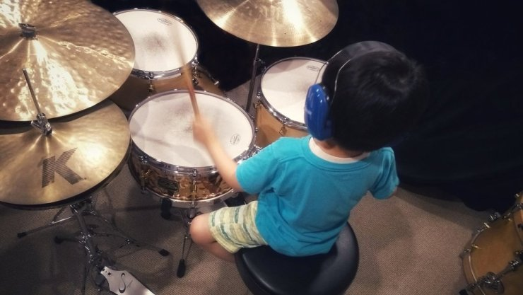A child wearing blue ear protection headphones is playing a drum set in a private lesson.