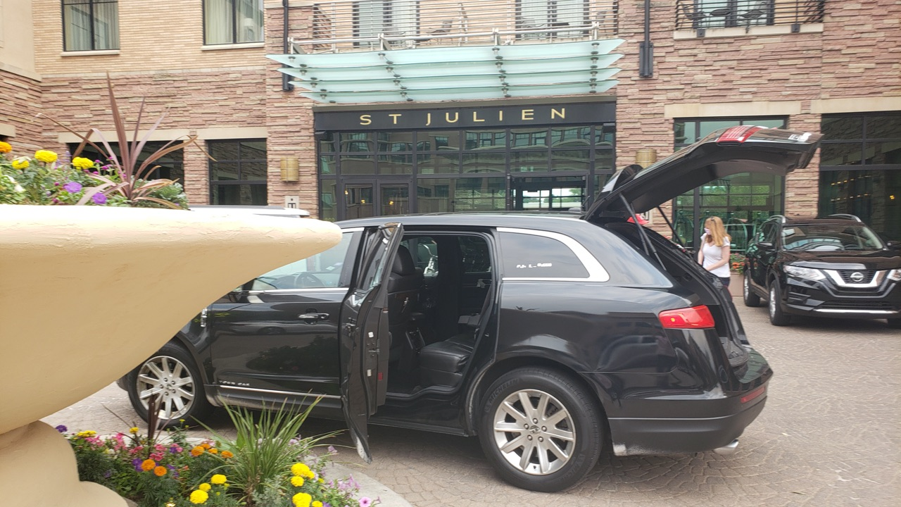passenger ready to board black sedan outside St Julien Hotel