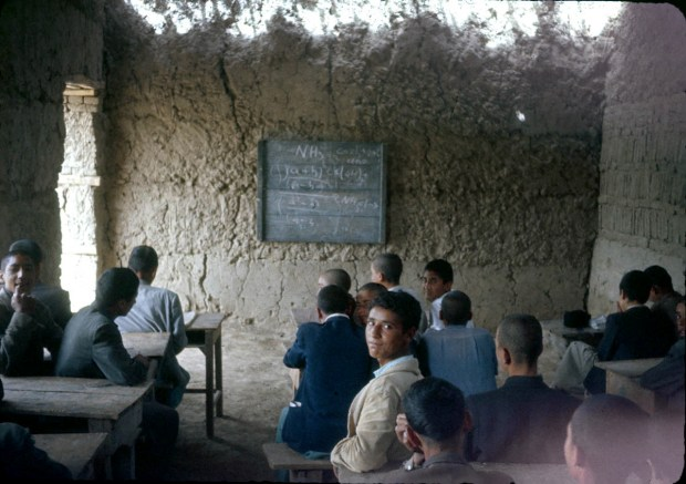 Chemistry lesson in a mud-walled classroom.