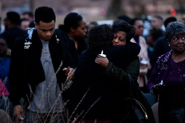 Tyler Clark holds his mothers hand as Heather Poole and her son take part in a candle light vigil at the Martin Luther King Jr. Cultural Center March 4, 2016 in Pueblo.