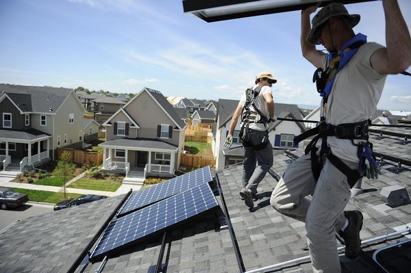 Workers from Namaste Solar install panels on a home in Denver in 2013.