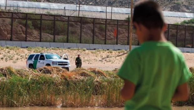 In this 2014 file photo a Mexican boy looks at a member of the U.S. Border Patrol standing guard on the border between El Paso, Texas, and Ciudad Juarez, Mexico.