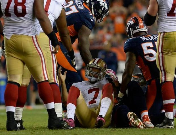 San Francisco 49ers quarterback Colin Kaepernick reacts after being sacked during an Oct. 19, 2014, game against the Broncos at Sports Authority Field at Mile High.