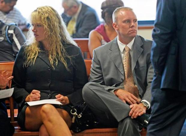 Denver police officer Jeremy Ownbey and his wife, Jamie Ownbey, wait at the Arapahoe County Justice Center for their arraignments, July 22, 2014.