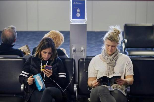 This 2015 file photo shows travelers using a charging station at McCarran International Airport in Las Vegas.