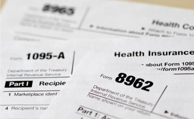 This Aug. 21, 2014, file photo shows health care tax forms 8962, 1095-A, and 8965, in Washington.