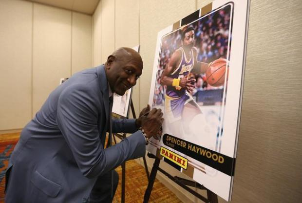 Spencer Haywood signs a print ahead ...