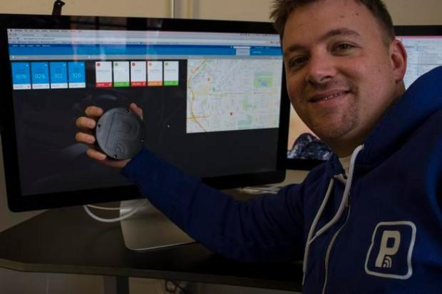 Parkifi co-founder Ryan Sullivan holds a sensor at the startup's office in downtown Denver. The sensors, which resemble hockey pucks, are installed in parking garages and lots so their owners can keep track of capacity.