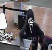 """This 2015 file photo shows two men wearing masks from the movie """"Scream"""" shoving guns in the faces of bank tellers."""