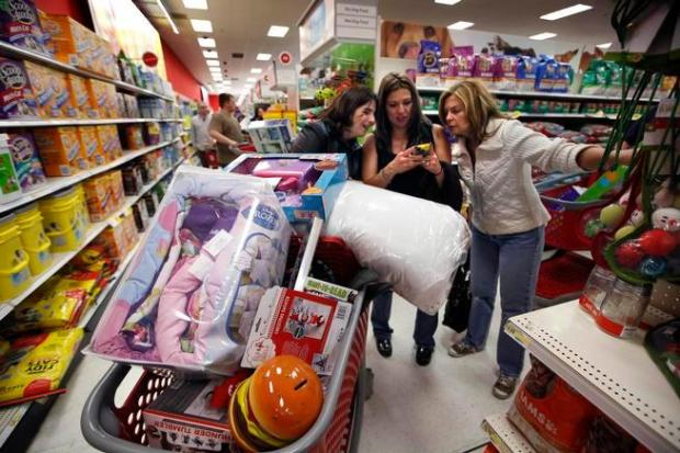 Target shoppers use a smartphone to compare competitor's prices on Black Friday, Nov. 28, 2014.