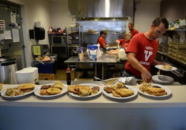 Volunteers cook and serve up breakfast at Urban Peak in this 2015 file photo.