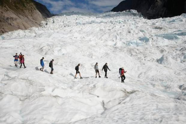 Tourists on a helicopter trip hike the Fox Glacier in New Zealand. The Fox and Franz Josef glaciers are melting at such a rapid rate that it has become too dangerous for tourists to hike onto them from the valley floor, ending a tradition that dates back a century.