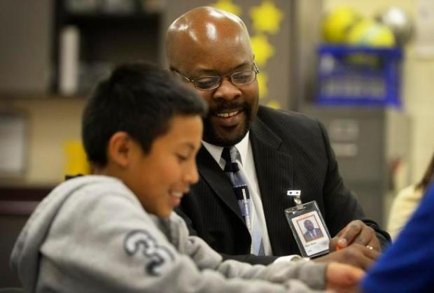 Aurora Public Schools Superintendent, Rico Munn, has a laugh with student, Wesley Tun-Medina, 12, during a math card game at North Middle School June 17, 2014.