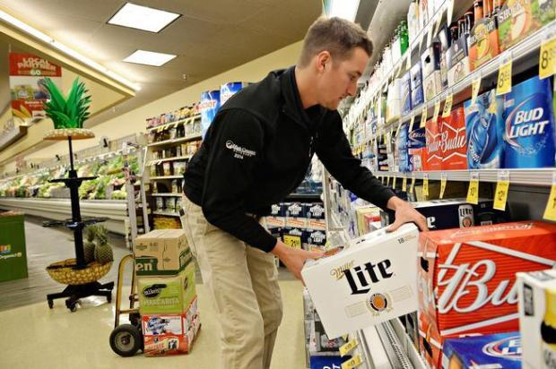 A beverage worker stocks 3.2 percent alcohol beer at a grocery store in Fort Collins.