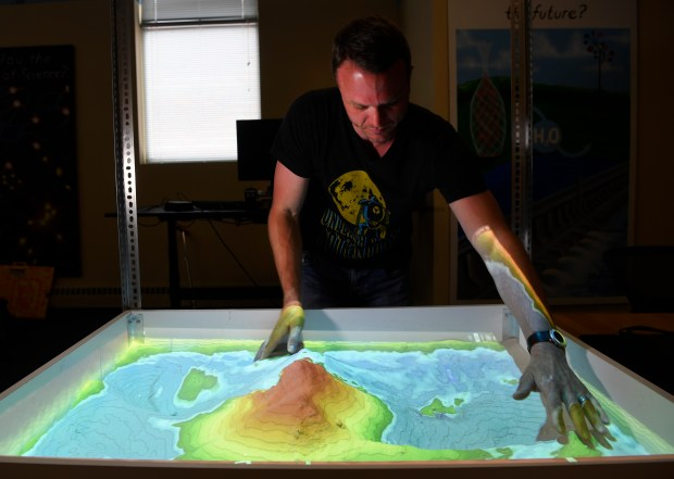 System76 CEO and founder Carl Richell makes a colorful topographical mountain of sand in the Augmented Reality Sandbox that System76 designed at its offices May 31, 2016.