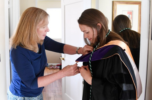 With the help of her mom Laurie Knight, left, Jennifer Knight, right, tries on her cap and gown that she will wear to her graduation from the University of Colorado law school.